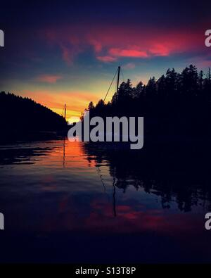 A rich and vibrant sunset fills the anchorage in Desolation Sound on a warm, summer night. - Stock Photo
