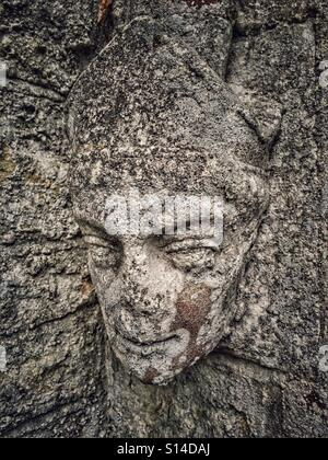 Weathered, carved stone head on the old school house, now the Village Hall, in Poyntington, Dorset.