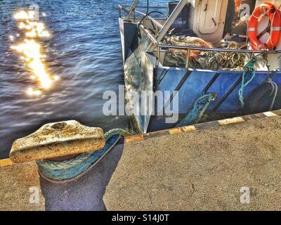Poller with trawler in morning sun - Stock Photo