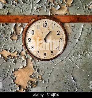 Clock in abandoned school in Pripyat ghost town, Chernobyl Nuclear Power Plant Zone of Alienation, Ukraine - Stock Photo