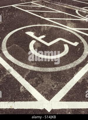 A grunge effect picture of a disabled person's car parking space. The symbol of a person sitting in a wheelchair - Stock Photo