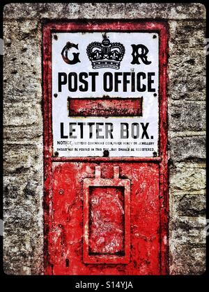 A high contrast image of an old post box in England, UK. The letters G & R next to the crown emblem identify the - Stock Photo