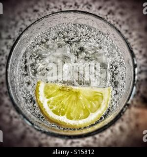 Gin and tonic with ice and a slice - Stock Photo