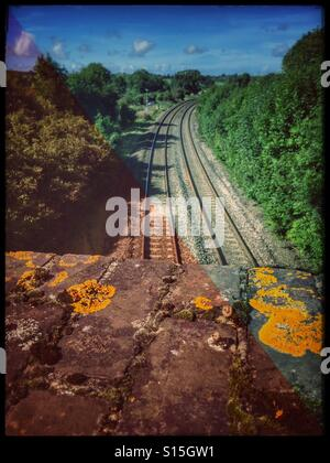 Looking down from old bridge onto train tracks - Stock Photo