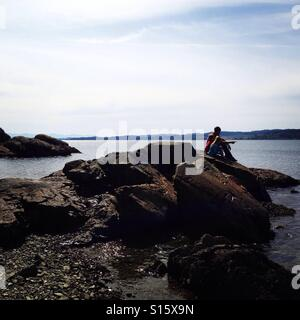 Man, boy and girl sitting on a rock looking at the ocean - Stock Photo