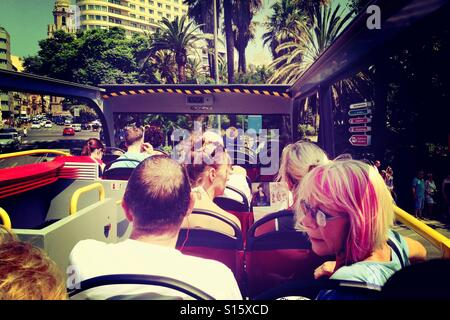 Tourists on an open top tour bus in Malaga Spain - Stock Photo