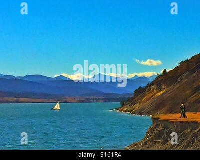 Small sail boat on Ghost Lake with the Canadian Rockies in the distance - Stock Photo