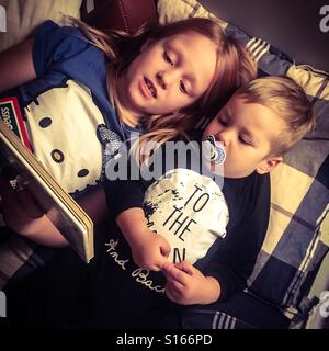 Siblings lying in bed reading a book together at nighttime - Stock Photo