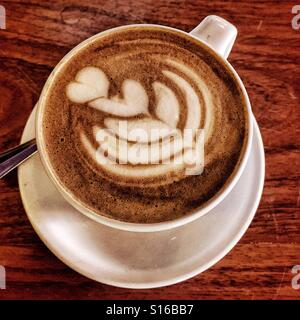 A beautifully artistic latte is viewed from above on a table at Cafe Brujula in Oaxaca, Mexico. - Stock Photo