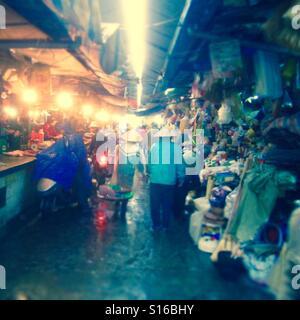 Couple walking through street market in Hanoi Vietnam - Stock Photo