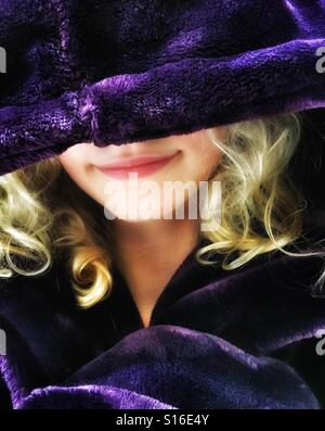 Girl snug in over sized purple dressing gown - Stock Photo