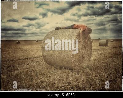 A muted colour picture of a 6 year old boy lying on a hay bale. He is in an open field & the storm clouds are brewing. - Stock Photo