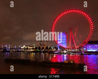 The London Eye lit up at night, from across the River Thames. - Stock Photo