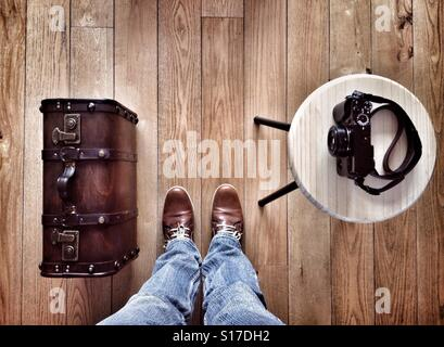 Man standing on a wooden floor next to him an Old suitcase and a photo camera - Stock Photo