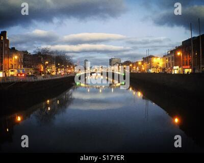 Ha'penny Bridge over the River Liffey in early evening. Dublin, Ireland - Stock Photo