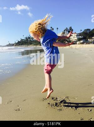 Girl leaping on beach - Stock Photo