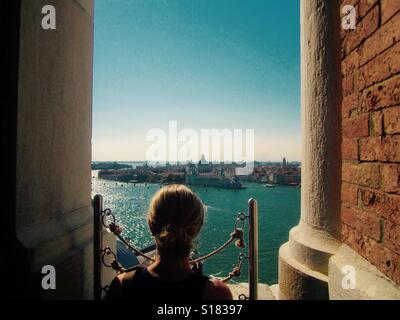 Woman looking out over Venice towards the Grand Canal - Stock Photo