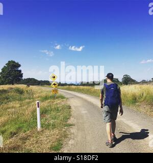 A hiker walks along the road on the Milanesia Track along the Great Ocean Walk in south west Victoria. - Stock Photo