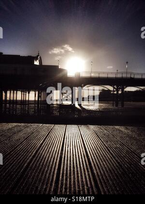 Wooden jetty and silhouetted pier. - Stock Photo