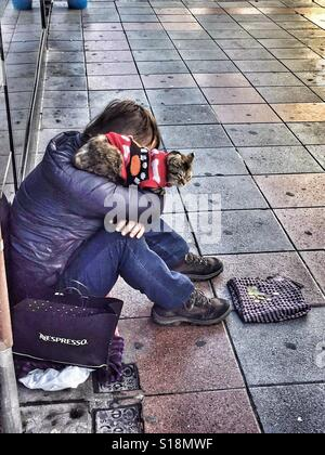 A beggar sits on the pavement in Alicante, Spain with a cat on his shoulder - Stock Photo