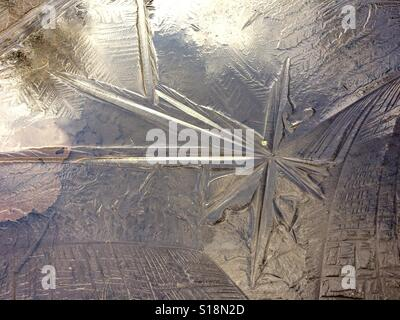 Ice patterns in frozen puddle - Stock Photo