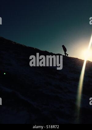 Boy walking up hill with sun shining - Stock Photo