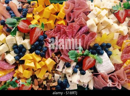 A large catered platter of assorted cheeses, cured meats, berries, and nuts. - Stock Photo