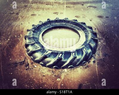 Washed up tractor tyre on beach - Stock Photo