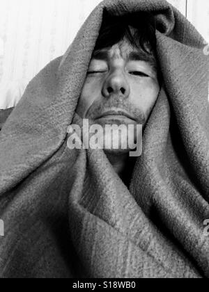 Sick man wrapped in blanket - Stock Photo