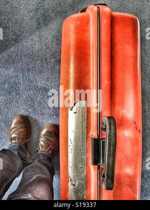 POV Feet  and battered red suitcase - Stock Photo