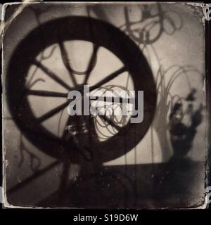 Stylized antique photograph of a spinning wheel used to spin thread - Stock Photo