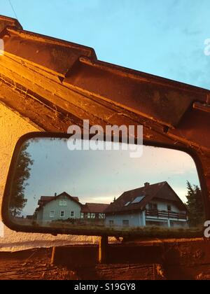 Reflection of a houses in a small mirror - Stock Photo
