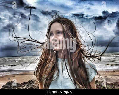 Pre-teen girl at the beach on a windy day. - Stock Photo
