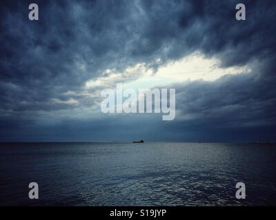 A storm brewing over placid waters - Stock Photo
