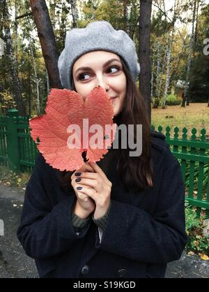 Young beautiful woman holding a big red leaf - Stock Photo