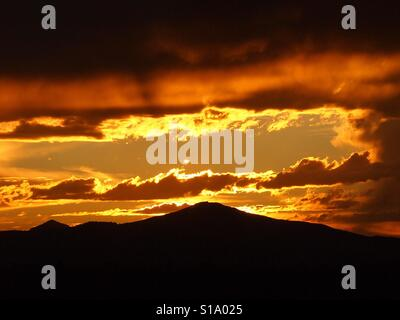 The Central Oregon Cascade Mountain Range at sunset after a storm causing different colors of red, yellow, gold, - Stock Photo