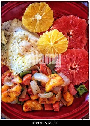 A plate is filled with a colorful variety of delicious breakfast foods including a fried egg, citrus slices, and - Stock Photo