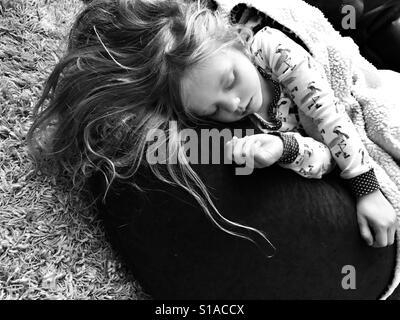 Little girl sleeping on a bean bag - Stock Photo