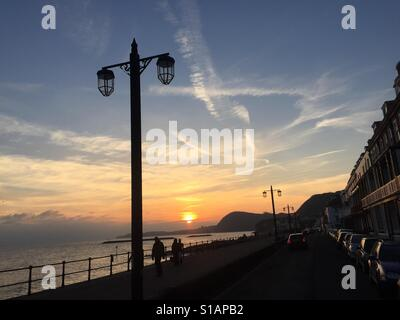 Sidmouth seafront along the promenade in the winter sun. East Devon natureshot. Sunset over the sea - Stock Photo
