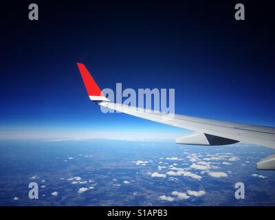 View through an aeroplane window of an airliner wing with a bright red wing tip, flying high above the clouds against - Stock Photo