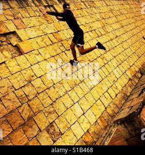 A Colombian parkour runner jumps on the wall during a free running training session held in a park in Kennedy, Bogotá, - Stock Photo