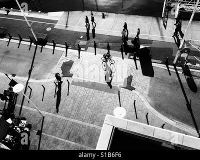 Black and white photo of the early morning sun casting long shadows as a cyclist rides along Poole Quay, Dorset, - Stock Photo