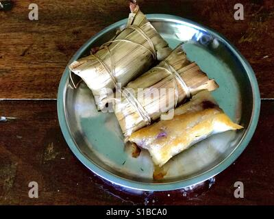 Local dessert from southern Thailand made of grilled sticky rice stuffed with banana - Stock Photo