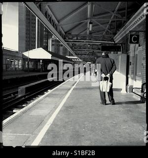 Man holding a bag on train station platform - Stock Photo