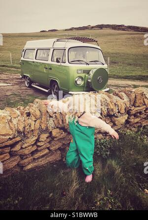 Young girl in green trousers next to a dry stone wall with a green type 2 bay window Vw camper van - Stock Photo