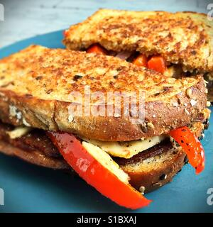 A sandwich made with vegan meat and cheese and grilled vegetables. - Stock Photo