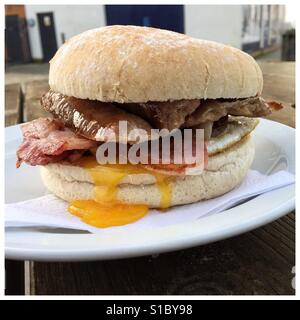 A tasty breakfast bap/roll from an outdoor cafe filled with bacon, sausage and egg. High in cholesterol and fat - Stock Photo