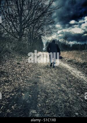 Man wearing a coat running away in the countryside - Stock Photo