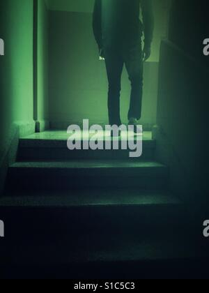 Rear view of a sinister male figure walking up the stairs - Stock Photo