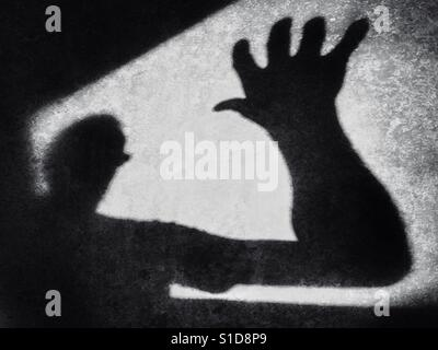 Shadowy figure making a grab. Conceptual image of fear of the unknown - Stock Photo